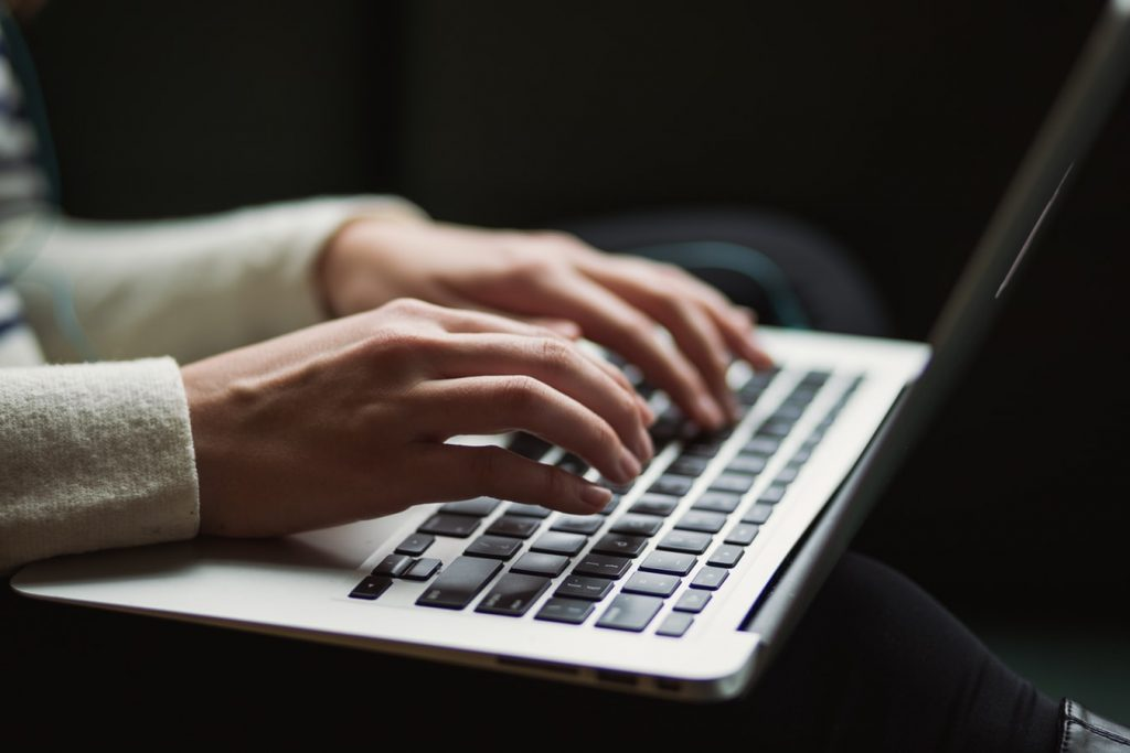 person blogging at a laptop